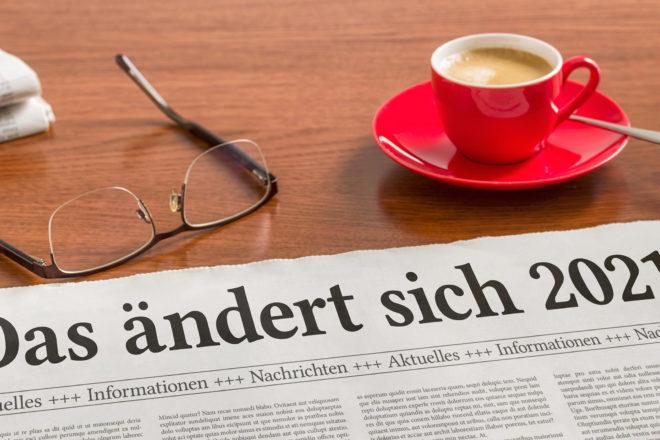 Foto zeigt eine Tasse Kaffee und eine Brille sowie eine Zeitung die über die neuen Gesetze 2021 und die Gesetzesänderungen 2021 informiert