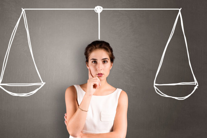 Foto zeigt Unternehmerin vor einer Tafel mit einer aufgezeichneten Waage als Symbol für das Abwägen von Pro oder Contra Kleinunternehmerregelung