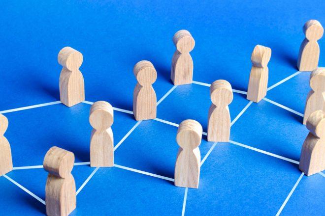 Das Foto zeigt Holzfiguren, die durch Linien miteinander verbunden sind. Sie sind ein Symbol für eine Zusammenarbeit im Betrieb. Gerade in der Krise lohnt sich die Entwicklung einer guten Personalstrategie. Wer jetzt die richtigen Schritte einleitet, profitiert im Aufschwung.