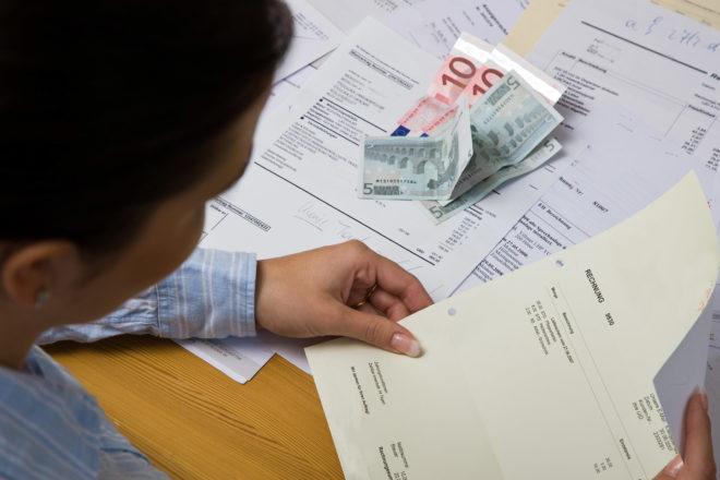 Foto zeigt einen Mann von schräg hinten und vor ihm Papier und Geldscheine bei der Bonitätsprüfung im Unternehmen
