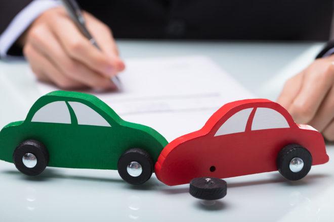 Foto zeigt zwei Modellautos beim Crash und dahinter eine schreibende Hand des Unternehmers, der den Unfall mit Firmenwagen schon vorher durchspielt