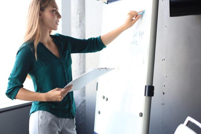 Foto zeigt junge Frau, die auf einem Whiteboard schreibt während einer Weiterbildung zur Nachwuchsförderung im Unternehmen