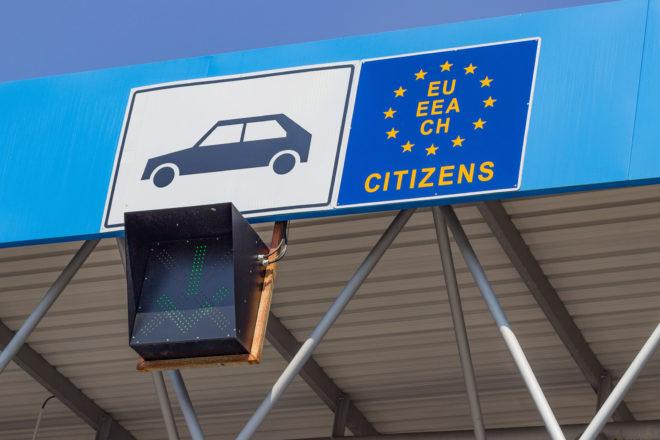 Foto von einem Grenzübergang mit EU-Flagge als Symbol für die A1-Bescheinigung bei Dienstreisen ins europäische Ausland, die auch jeder Unternehmer, Selbständige und Geschäftsführer braucht.