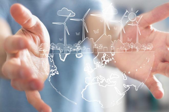 Foto von Händen, die Windräder umfassen, als Symbol für Energieeffizienz in Unternehmen