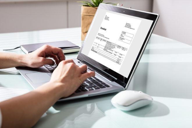 Foto zeigt Hände auf einer Laptoptastatur - auf dem Monitor eine Kleinbetragsrechnung