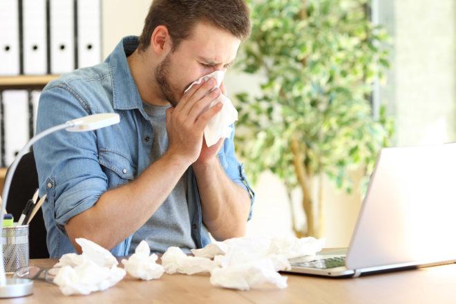 Foto zeigt einen sich schnäuzenden Mann mit benutzten Taschentüchern vor sich und seinem Laptop zum Artikel über Lohnfortzahlung bei Krankheit