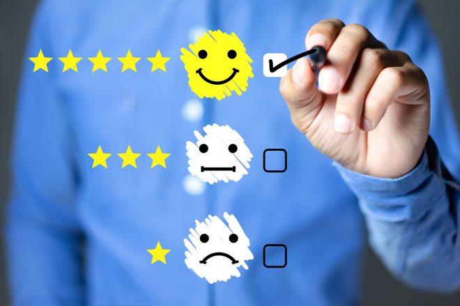 Das Foto von drei unterschiedlichlich glücklichen Smileys vor der Brust eines Menschen symbilisiert das Thema Mitarbeiterbeurteilung