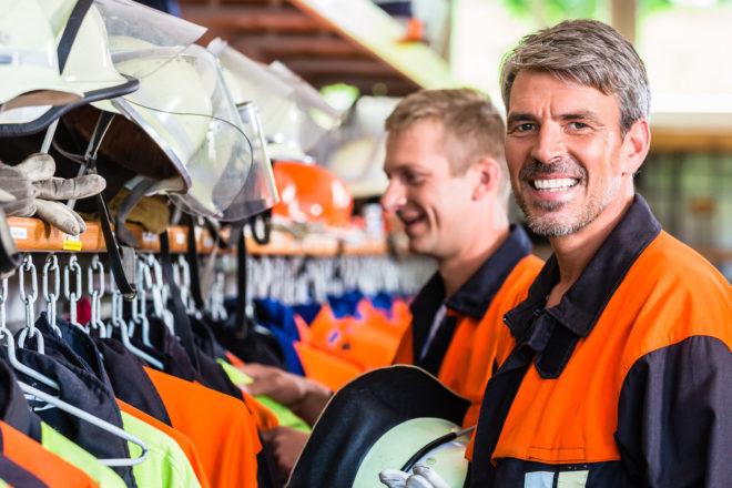 Foto zeigt zum Thema Freistellung für das Ehrenamt einen lächelnden Feuerwehrmann beim Ankleiden