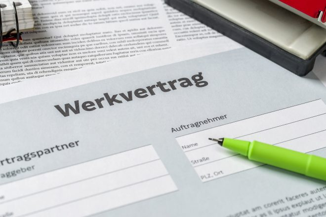 Foto zeigt einen grünen Kugelschreiber auf einem Formular namens Werkvertrag liegend
