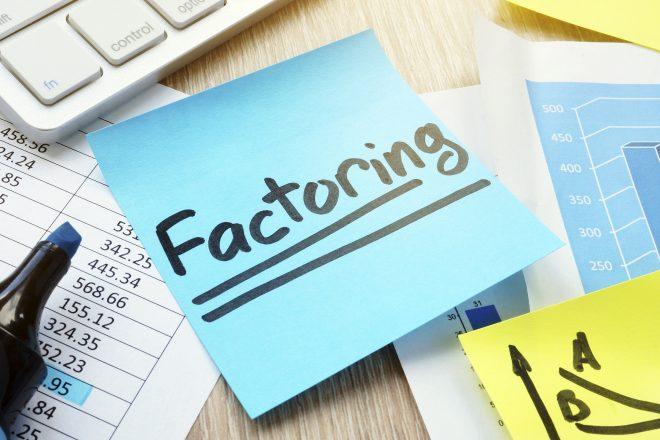 Foto zeigt eine Tastatur und die Spitze eines blauen Textmarkers, die auf eine Haftnotiz mit der Aufschrift Factoring zeigt