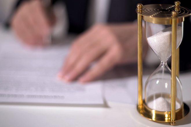 Foto zeigt eine Sanduhr neben den schreibenden Händen eines Mannes im Anzug zu einem Artikel zum Thema Zeitarbeit