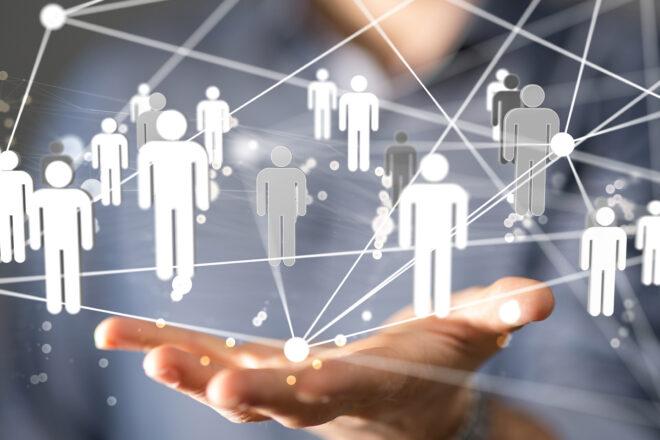 Fotomontage zeigt Hand die ein Netzwerk aus Figürchen hält zum Thema Arbeitnehmerüberlassungsgesetz