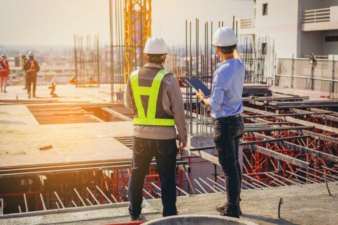 Foto zeigt zwei Männer mit Schutzhelm, die eine Baustelle begutachten vielleicht zur Begutachtung eines Schadens, den eine Versicherung für Berufshaftpflicht auf für Freiberufler wie Architekten oder Ingenieure reguliert