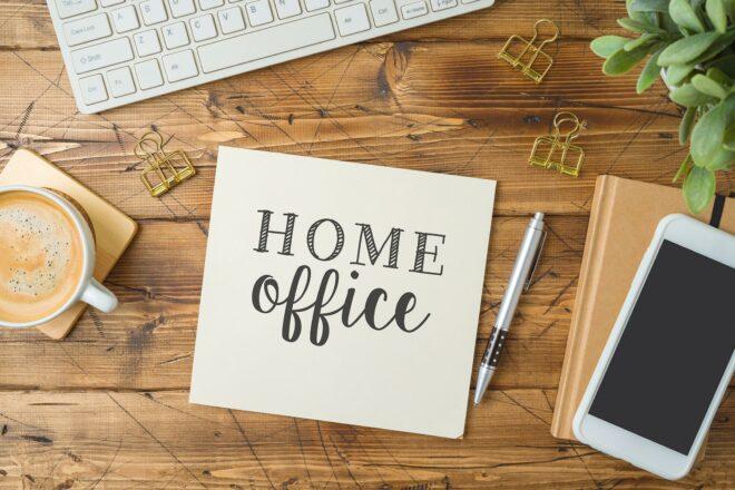 Symbolfoto zeigt ein Post-It mit der Aufschrift Homeoffice auf dem Küchentisch neben dem Laptop