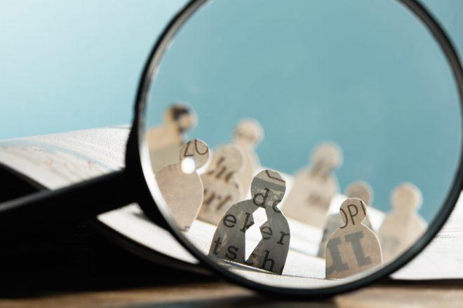 Fotomontage zeigt eine Lupe, mit der HR- und Personalverantwortliche im Rahmen ihres Talent Management laut Definition Talente oft erst mal suchen