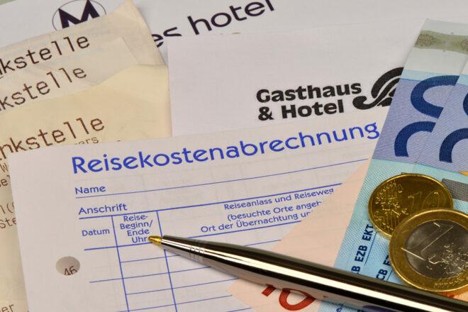 Foto zeigt wie es beim Abrechnen der Reisekosten aussieht - ein Kugelschreiber auf dem Formular Reisekostenabrechnung und darunter ein Stapel Tankbelege und Hotelrechnungen