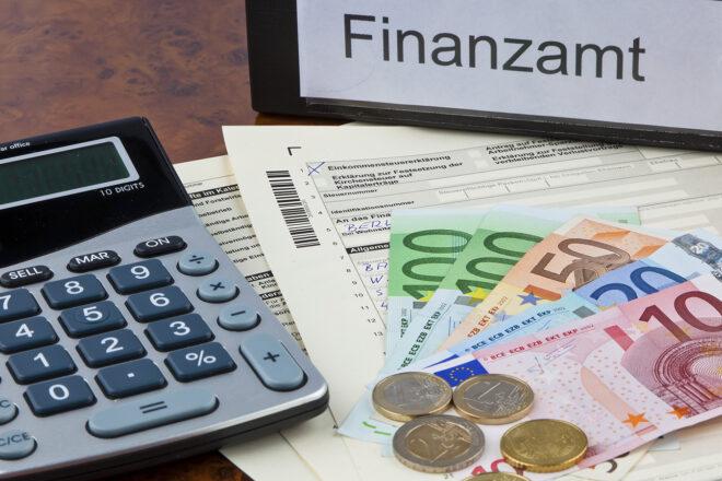Foto mit Taschenrechner, Geöd und Finanzamtsorder als Symbol dafür, dass Selbständige auch Steuern zahlen müssen