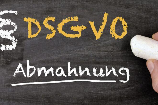 Die Worte DSGVO und Abmahnung werden mit Kreide neben einem Paragrafenzeichen auf eine Tafel geschrieben als Symbol für eine durch Abmahnwälte ausgelöste Abmahnwelle, die Kosten in beträchtliher Höhe verursachen kann.
