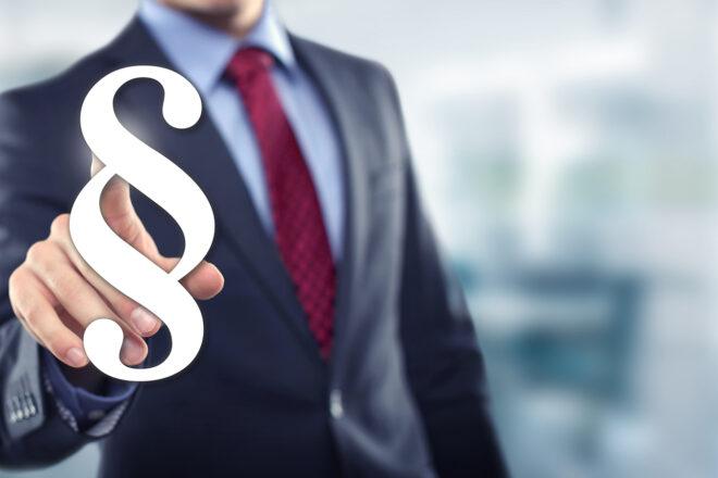 Foto von einem Mann, der auf einen Paragrafen tipt, als Symbol für die ordentliche Kündigung von einem Arbeitsvertrag durch den Arbeitgeber.