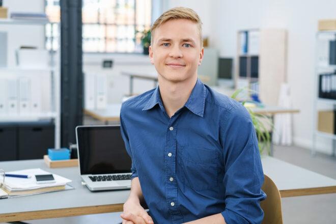 Bild zeigt jungen Mann an einem Rechner im Unternehmen als Symbol für das Privileg von Werkstudenten in der Sozialversicherung