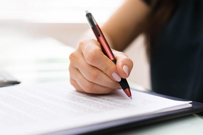 Foto zeigt Frauenhand, die mit einem Kugelschreiber den Vertrag für einen Rechtsformwechsel ihres Unternehmens signiert