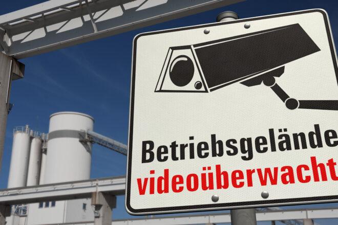 Foto zeigt ein Hinweisschild auf die Videoüberwachung auf dem Firmengelände vor blaubem Himmel